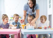 小组吃健康食品午休时间的托儿所婴孩与幼儿园老师一起 库存照片