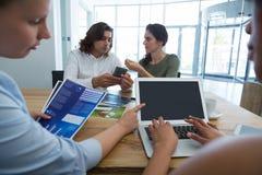 小组同事谈论在手机和膝上型计算机在书桌 图库摄影