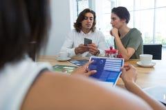 小组同事谈论在手机 免版税库存照片