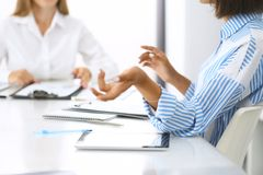 小组商人在会议上在办公室,特写镜头 谈论两名的妇女队成交 交涉概念 免版税库存图片