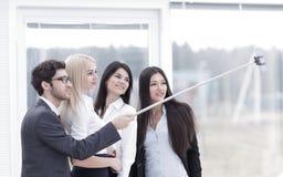 小组商人在办公室喜欢采取与队工作的Selfie在见面以后 免版税库存照片