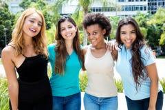 小组四名国际笑的年轻妇女 库存图片