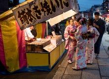 小组在一个报亭的艺妓购买在街道上 免版税库存图片
