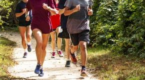 小组在土足迹跑的赛跑者 库存照片