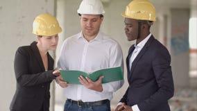 小组在安全帽的微笑的建造者有剪贴板和图纸的户外 股票视频