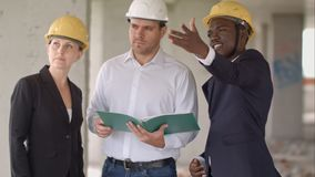 小组在安全帽的微笑的建造者有剪贴板和图纸的户外 免版税图库摄影