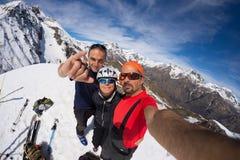 小组在山上面的登山家selfie 在雪的风景高处背景加盖了阿尔卑斯,晴天 免版税库存图片
