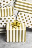 小组在白色的礼物和在灰色背景的金纸 库存照片