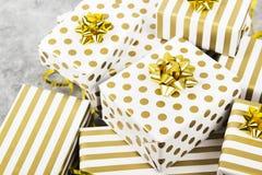 小组在白色的礼物和在灰色背景的金纸 免版税库存图片