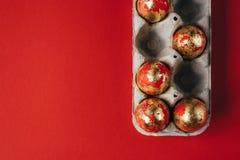 小组在纸板鸡蛋箱子的红色和金子被绘的复活节彩蛋 库存图片