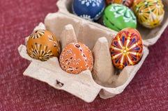 小组在纸板鸡蛋箱子的被绘的复活节彩蛋,复活节彩蛋狩猎庆祝,在纸箱的五颜六色的静物画 图库摄影