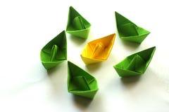 小组在绿色和黄色颜色的origami纸船 库存照片