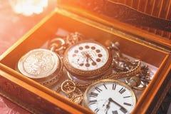 小组在链子的古色古香的葡萄酒手手表在木箱,减速火箭的典雅的时钟 库存照片