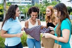 小组在黑星期五购物以后的四名妇女在城市 免版税库存照片