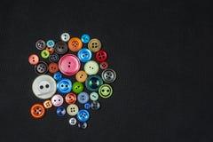 小组在黑暗后面的多彩多姿和不同的大小的按钮 免版税库存图片