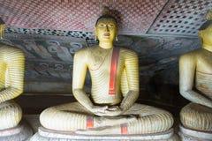 小组坐在洞佛教寺庙的菩萨雕象 免版税库存图片