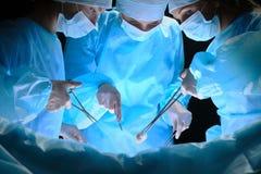 小组外科医生在工作在手术室在蓝色定了调子 免版税库存图片