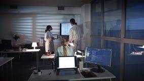 小组多种族电子工程师谈论某事在一个大电视屏幕上在电子实验室