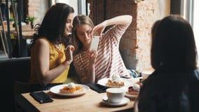 小组女朋友照相用在咖啡馆的食物使用智能手机照相机 股票录像