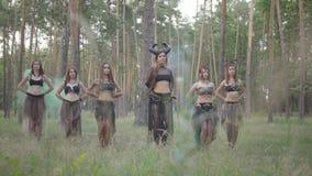 小组妇女舞蹈家有构成的和跳舞在颜色烟的神秘的美妙的服装的 森林神仙,树精 股票录像