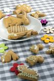 小组姜饼动物和标志在白色板材在方格的桌布,两个兔宝宝在爱,复活节彩蛋狩猎 库存图片