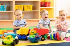 小组婴孩在地板上使用在托儿所 孩子在日托中心 在儿童` s游戏室的乐趣 免版税库存图片