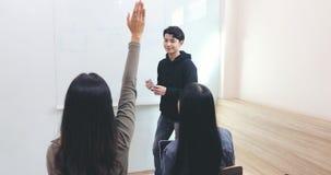 小组学生在教室举他们的手要求朋友问题教在whiteboard 库存图片