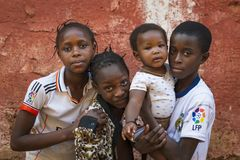 小组孩子他们的Cupelon de Cima邻里的家外在市比绍 库存图片