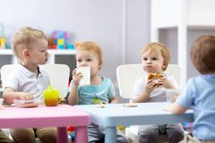 小组孩子在托儿所的吃食物 免版税库存图片