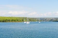 小组宪章乘快艇,帆船在海近的岸 库存照片