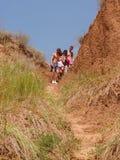 小组山的远足者 帮助她的朋友的妇女攀登岩石 山远足的青年人在日落 免版税图库摄影