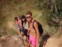 小组山的远足者 帮助她的朋友的妇女攀登岩石 山远足的青年人在日落 免版税库存照片