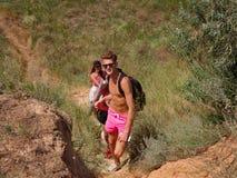 小组山的远足者 帮助她的朋友的妇女攀登岩石 山远足的青年人在日落 库存照片