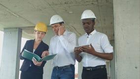小组工程师和专家谈论关于建造场所 免版税图库摄影