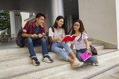 小组年轻亚洲学习在坐在lectu期间的大学 免版税库存图片