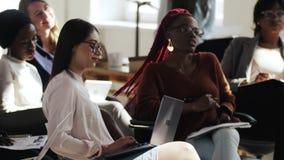 小组年轻愉快的不同种族的同事妇女,听控制讲话在现代轻的办公室事件 股票录像
