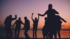 小组年轻跳舞人民剪影有一个党在日落的海滩 图库摄影