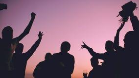 小组年轻跳舞人民剪影有一个党在日落的海滩 免版税图库摄影