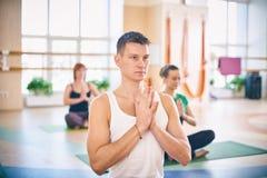 小组年轻运动的与辅导员的人民实践的瑜伽教训,坐在Padmasana锻炼,莲花姿势用被折叠的手我 免版税库存照片