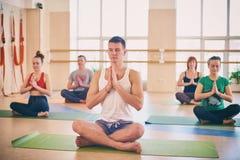 小组年轻运动的与辅导员的人民实践的瑜伽教训,坐在Padmasana锻炼,莲花姿势用被折叠的手我 免版税库存图片