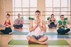 小组年轻运动的与辅导员的人民实践的瑜伽教训,坐在Padmasana锻炼,莲花姿势用被折叠的手我 库存照片