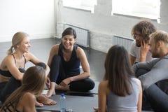 小组年轻运动的微笑的人民谈话在瑜伽以后分类 免版税库存照片