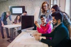 小组年轻透视设计师谈论在办公室 图库摄影