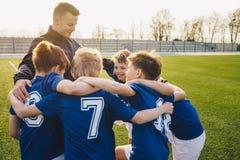 小组庆祝与教练的足球队员的孩子 库存照片
