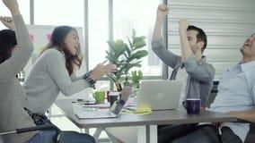 小组快乐的愉快的亚裔创造性的女商人和人享用和有乐趣跳舞,当工作在她的办公室时 股票视频