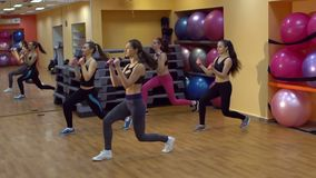 小组愉快的女孩在与哑铃的健身房训练 股票录像