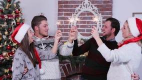 小组愉快的朋友拿着孟加拉光和微笑,佩带圣诞节帽子,庆祝圣诞节和新年 影视素材