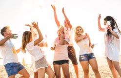 小组愉快的朋友获得乐趣在holi颜色的海滩党 免版税库存照片