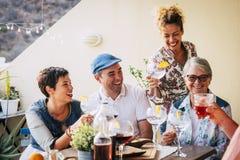 小组成人在大阳台混合了从40的年龄到80在家一起庆祝用食物和酒 一起友谊人 免版税库存照片