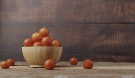 小组成熟蕃茄在木桌的木碗地方 免版税库存照片